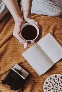 woman holding mug of coffee beside opened book