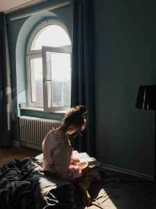 woman sitting while reading a book
